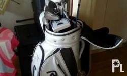 A set of golf clubs, wood, hybrid, iron wedge and