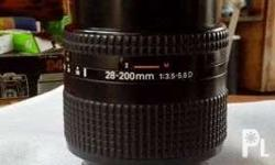 Nikkor lens 28-200mm 3.5-5.6D with front and rear cap.
